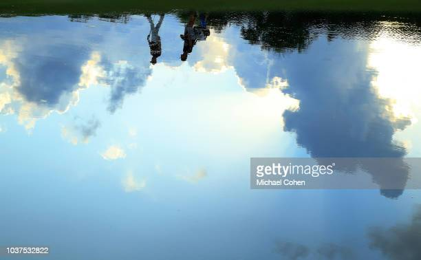 The reflection in the pond of a player walking with his caddie near the 10th green during the second round of the Web.com Tour Championship held at...