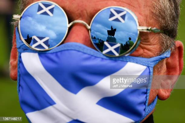 The reflection is seen in the glasses of a supporter of Scottish independence as they gather at the site of the battle of Bannockburn for an 'All...