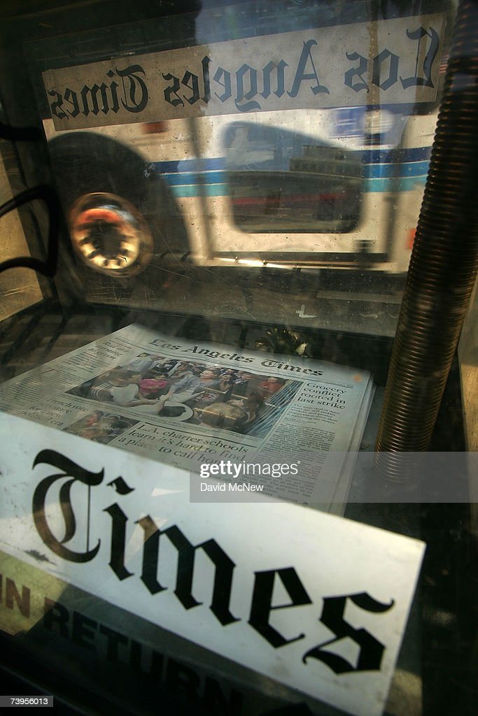 The reflection of a bus passes a rack of Los Angeles Times newspapers for sale April 23, 2007 in Los Angeles, California. The Times announced today that it will offer voluntary buyouts in an effort to cut its staff of 2,625 by up to 150. Up to about 70 of those jobs would be in the newsroom, dropping the news staff to about 850. When the Tribune Co. bought the newspaper in 2000, there were 1,200 employed on the news side. Last fall, publisher Jeffrey M. Johnson and then Editor Dean Baquet were forced from the paper for fighting against cuts in the newsroom and arguing that a reduction of reporters and editors would hurt the quality of the paper, a belief contrary to that of Tribune executives.