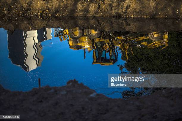 The reflection of a Caterpillar Inc 120H motor grader machine is seen during construction outside of Olympic Park in Rio de Janeiro Brazil on...