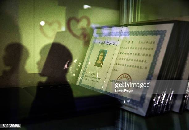 The reflection of a Chinese woman training to be a qualified nanny known in China as ayis is seen in the glass of a cabinet with the certificates of...