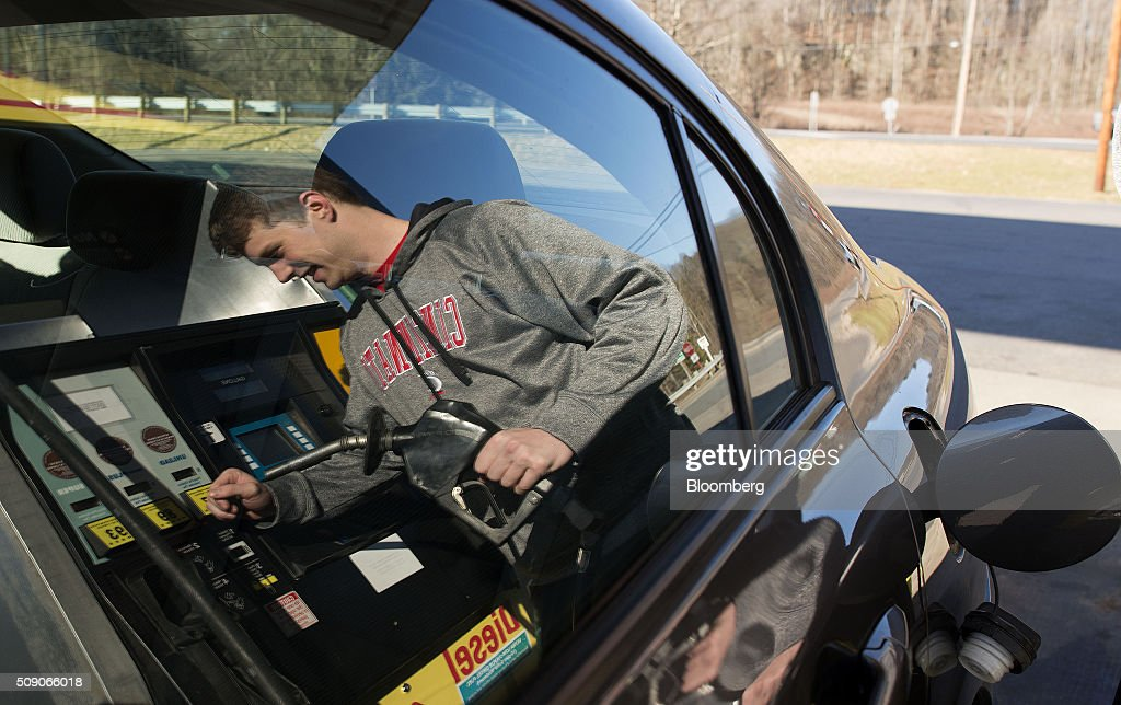 The reflection of a customer is seen on a the window of a vehicle at a Go Mart Inc. gas station in Rockbridge, Ohio, U.S., on Saturday, Feb. 6, 2016. Thanks to a glut of oil that has spurred refiners to make as much fuel as they can, pump prices nationwide are down about 26 cents a gallon from a year ago, which is translating into almost $80 million a day in savings for U.S. drivers, according to Michael Green, a spokesman in Washington for AAA. Photographer: Ty Wright/Bloomberg via Getty Images