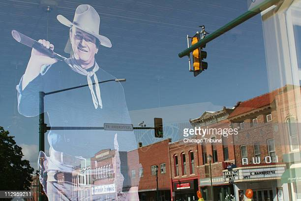 The reflection of a John Wayne figure is seen in the window of the Chamner of Commerce in Winterset Iowa his birthplace