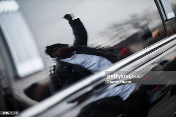 The reflection of a man raising his fist as the funeral procession for Jamar Clark passes by outside the 4th Precinct Minneapolis Police station on...