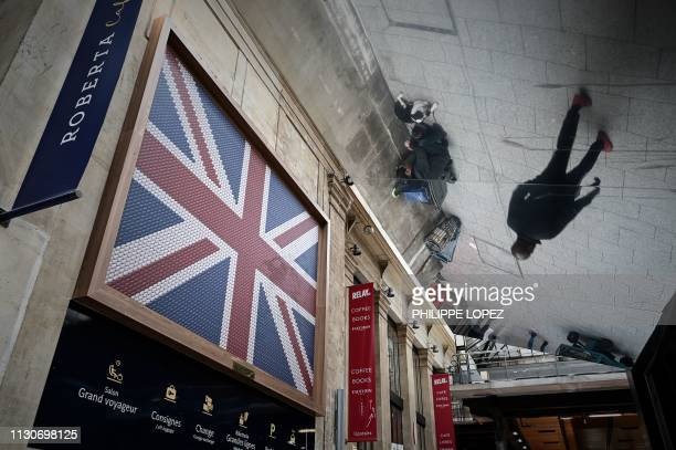 The reflection of a man walking past a British flag is seen near the entrance of the Eurostar terminal at the Gare du Nord railway station in Paris...