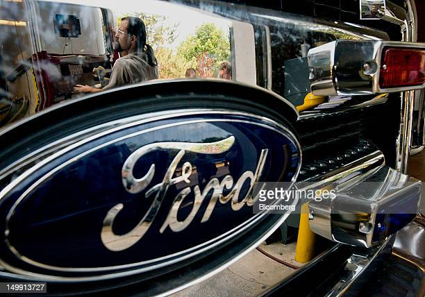 The reflection of an employee is seen on the grill of a Ford Motor Co ambulance at the Horton Emergency Vehicles facility in Grove City Ohio US on...