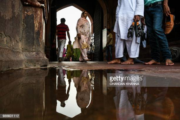 The reflection of an Indian woman is seen in a puddle of water as she walks inside the Jama Masjid in the old quarters of New Delhi on March 21 2018...