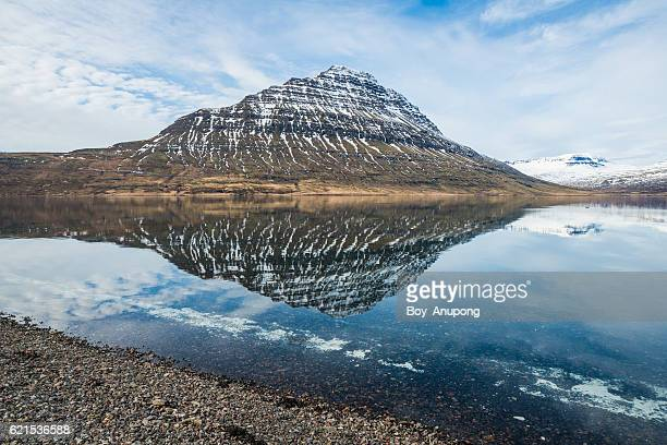 The reflection of Holmatindur the iconic mountain of Eskifjordur town of East Iceland.