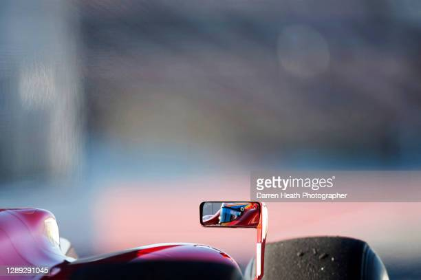 The reflection of Spanish Ferrari Formula One racing driver Fernando Alonso seen in the right rear view mirror of his Ferrari F10 racing car as he...