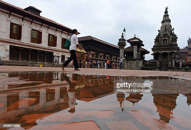 The reflection of the Bhaktapur Durbar square an ancient royal palace is seen in a puddle of water following rainfall as a Nepalese pedestrian walks...