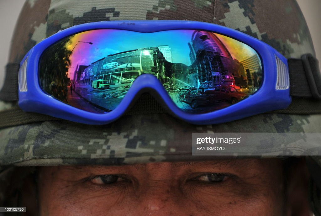 The reflection on a Thai army soldier's sunglasses shows the burnt down Central World shopping mall in downtown Bangkok on May 21, 2010. Thailand picked up the pieces after violence and mayhem triggered by a crackdown on anti-government protests, as the focus swung to recovery and reconciliation in a divided nation. AFP PHOTO / Bay ISMOYO