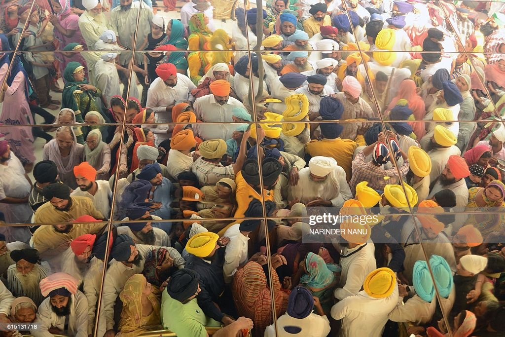 TOPSHOT The reflection on the ceiling shows Indian Sikh devotees gathering to pay respects as a `Jalau` ritual takes place inside the Sikh Shrine...