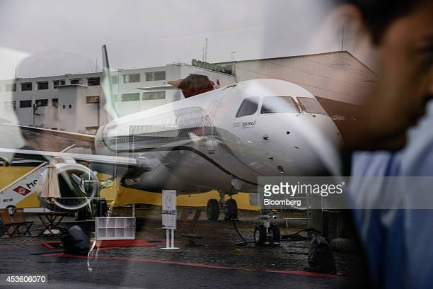 The reflections of attendees are seen at Embraer's Empresa Brasileira de Aeronautica SA exhibit during the Latin American Business Aviation...