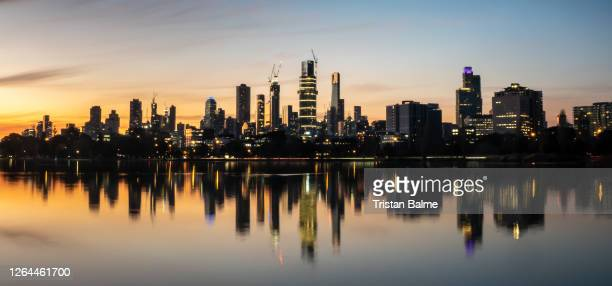 the reflections of the melbourne city skyline at dusk in the still water of albert park lake - melbourne australia stock pictures, royalty-free photos & images