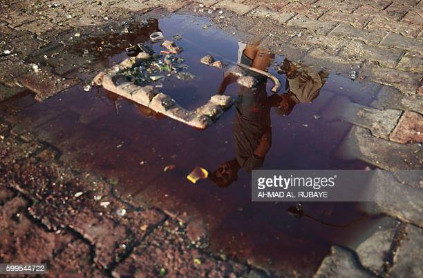 TOPSHOT The reflexion of an Iraqi youth is seen on a pool of blood and water on September 6 2016 in the aftermath of a car bomb explosion in the...