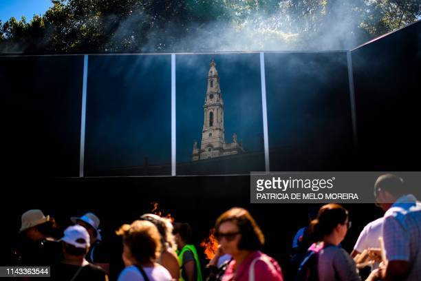 The reflexion of Fatima´s shrine is pictured as people throw candles in the fire in Fatima central Portugal on May 12 2019 Thousands of pilgrims...