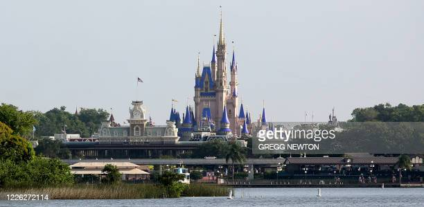 The refurbished Cinderella Castle rises above Bay Lake at the Magic Kingdom theme park at Walt Disney World on the first day of reopening, in...