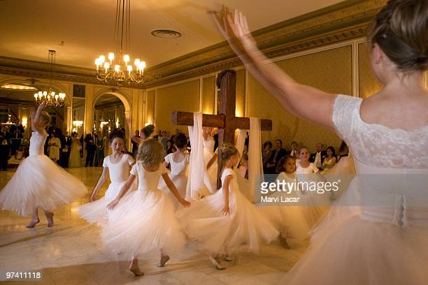 The Regal Daughters Ballet Company dance around the wooden cross in the ballroom of the Broadmoor Hotel on May 16 2008 in Colorado Springs Colorado...