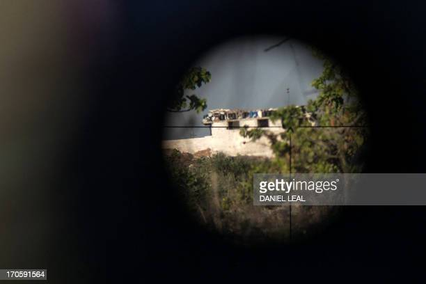 The regimecontrolled military base of Wadi Deif is displayed on June 14 2013 through the scope of a rebel fighter rifle from a trench in the village...