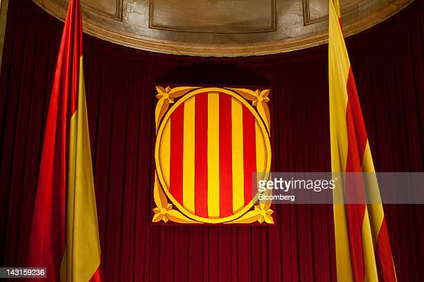 The regional flag of Catalonia right hangs beside a Spanish national flag left in the assembly hall at the Catalan parliament in Barcelona Spain on...