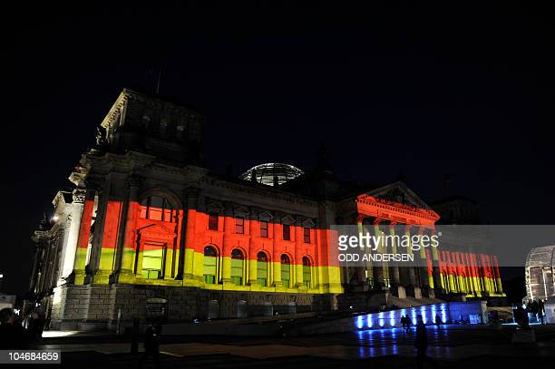 The Reichstag is illuminated in the colours of the German flag during a ceremonial event marking the 20th anniversary of the reunification of Germany...