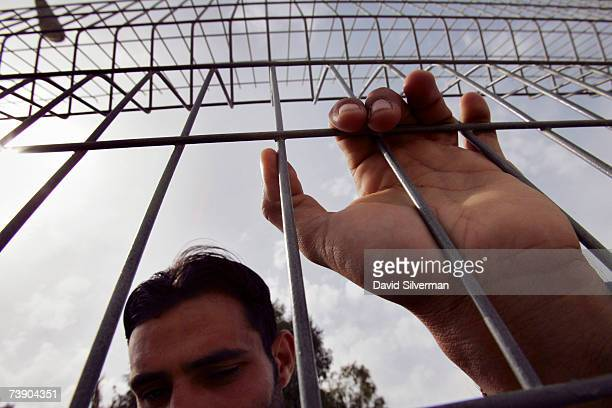 The relative of a Palestinian prisoner holds onto the fence of a waiting compound as he waits to be called to see his incarcerated family member...