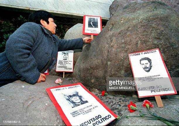 The relative of a political prisoner killed during the 1973-1990 Pinochet dictatorship, lays a flower near a victim's portrait at the foot of the...