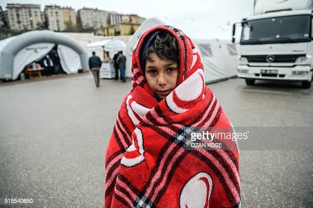 The relative of a victim wrapped in a blanket stands outside the forensic building as he waits for the body of a relative on March 14 2016 in Ankara...