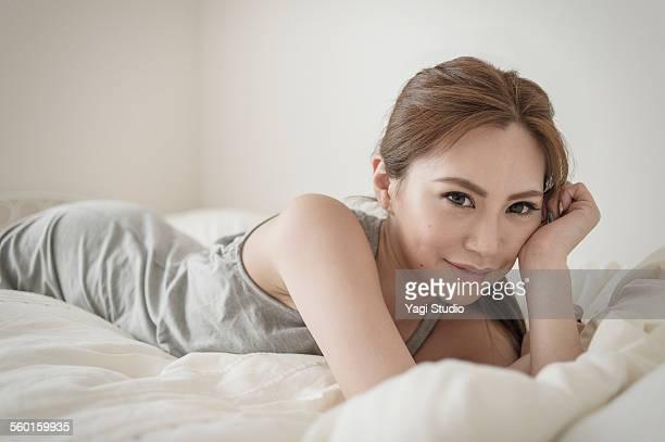 the relaxing woman lying on bed - acostado boca abajo fotografías e imágenes de stock