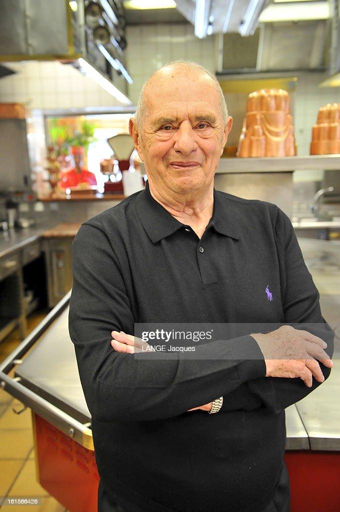The Relay Bernard Loiseau Celebrates Its 20th Anniversary At Bocuse. Paul BOCUSE a invité dans son établissement de COLLONGES-AU-MONT-D'OR Dominique LOISEAU et son équipe pour fêter le 20ème anniversaire du restaurant Relais Bernard Loiseau (avant La Côte d'Or) de Saulieu, toujours trois étoiles au Michelin et ce, malgré la mort de Bernard Loiseau en 2003 : plan de face souriant de Paul BOCUSE posant bras croisés, en polo noir, dans les cuisines du restaurant.