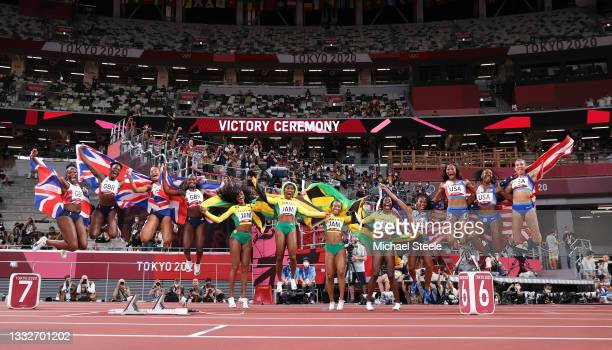 The relay runners representing Team Great Britain, Team Jamaica and Team United States celebrate winning their respective medals after the Women's 4...