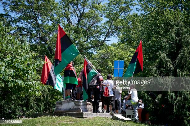 The remaining base of where before a statue of Christopher Columbus stood forms the stage for a Black Lives Matter protest rally organized by Black...