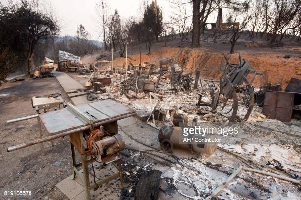 The remains of a burned property smolders in Mariposa California on July 19 2017 The Detwiler fire is currently at 7 percent containment and has...