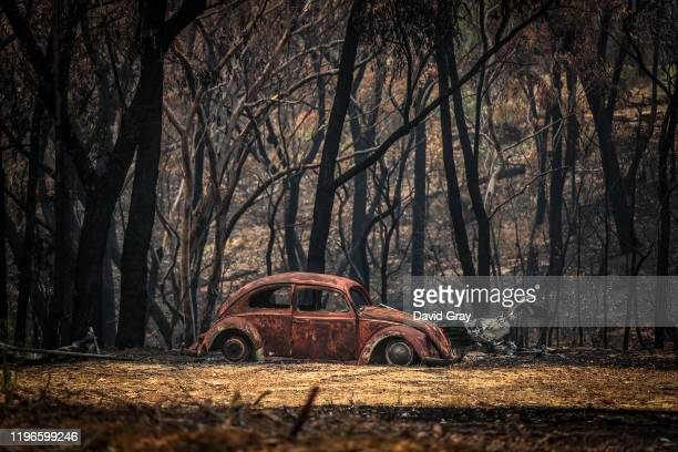 The remains of a car that was destroyed by bushfires sits near a home in the town of Balmoral on December 30 2019 in Sydney Australia Firefighters...