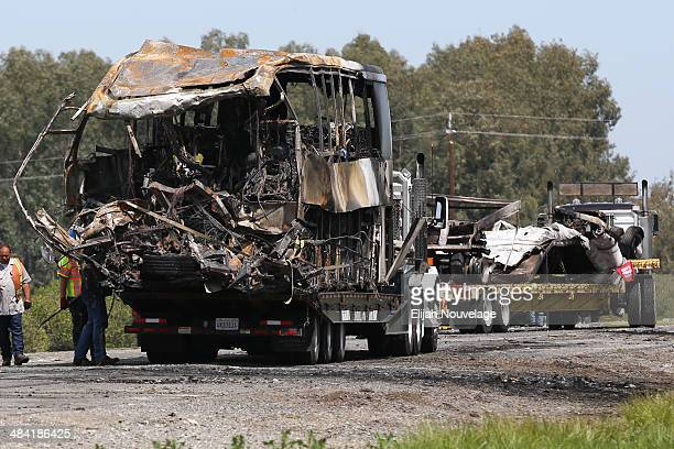 The remains of a FedEx truck right and bus left involved in Thursday's deadly crash are seen on trucks at the scene of the accident on April 11 2014...