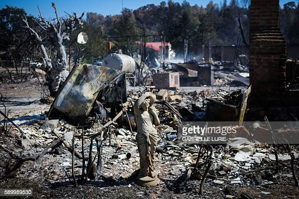 TOPSHOT The remains of a house destroyed in the Clayton Fire are seen in Lower Lake California August 15th 2016 A northern California wildfire grew...