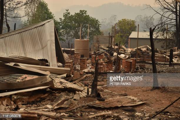 TOPSHOT The remains of a property destroyed by fire is seen in Bobin 350km north of Sydney on November 9 as firefighters try to contain dozens of...