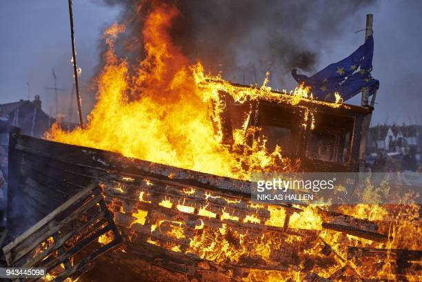 TOPSHOT The remains of a small boat flying European flags is burnt on a bonfire during a demonstration in Whitstable southeast England on April 8...
