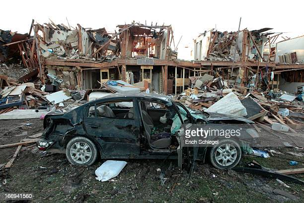 The remains of an apartment complex and a destroyed car lies in ruins next to the fertilizer plant that exploded yesterday afternoon on April 18 2013...
