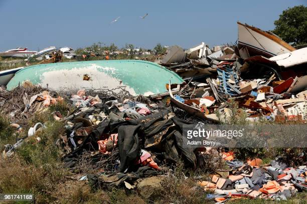 The remains of boats used by refugees in their attempted crossings from Turkey to Greece lay amongst thousands of used life preservers and pieces of...