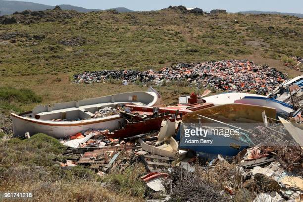 The remains of boats used by refugees in their attempted crossings from Turkey to Greece lay among thousands of used life preservers and pieces of...