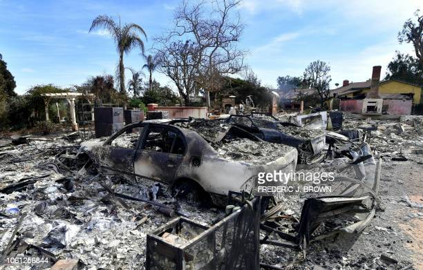 TOPSHOT The remains of burnt down homes and vechicles resulting from the Woolsey Fire are seen on Busch Drive in Malibu California on November 13...