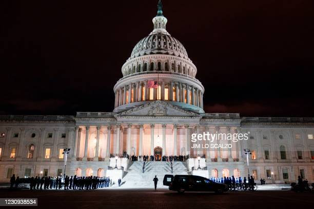 The remains of Capitol Police Officer Brian Sicknick are carried up the the East Front steps prior to lying in honor in the Rotunda of the Capitol in...