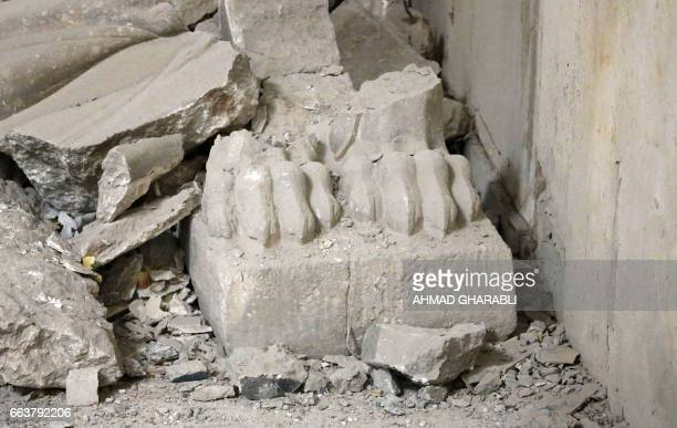The remains of carved feet of a Lamassu statue an Assyrian deity often depicted as a wingedbull with a human head stands inside the destroyed museum...