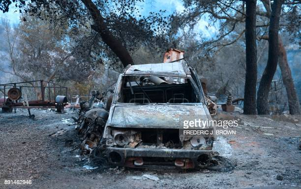 The remains of fire damaged vehicles remain outside a home in the hills of Toro Canyon north of Santa Barbara California on December 12 2017 as...
