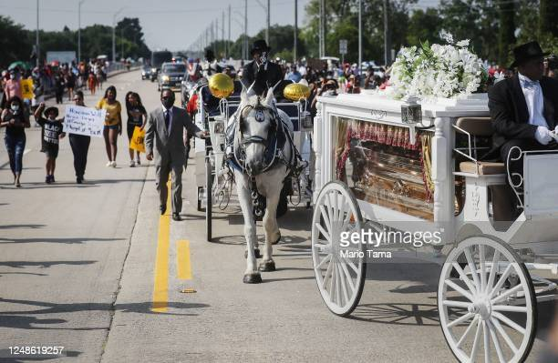 The remains of George Floyd are brought by horsedrawn carriage in a funeral procession to Houston Memorial Gardens Cemetery for burial on June 9 2020...