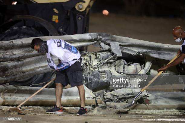 The remains of Haas F1's French driver Romain Grosjean's car are seen through the barriers after crashing at the start of the Bahrain Formula One...