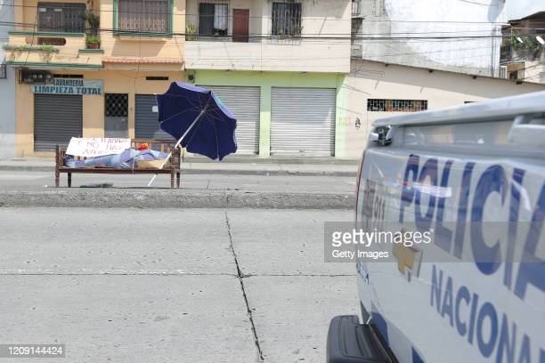 The remains of María Zamora who passed away of a heart attack lies on a public bench at one of the main streets in the south of Guayaquil with a sign...