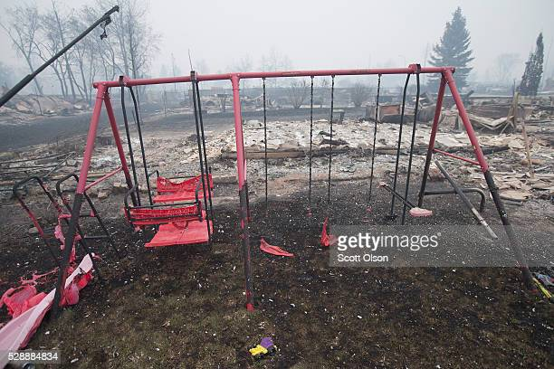 The remains of partiallymelted swing set sit in a residential neighborhood heavily damages by a wildfire on May 7 2016 in Fort McMurray Alberta...