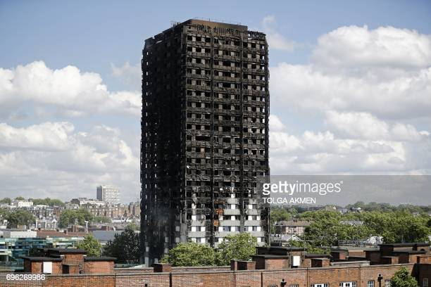 TOPSHOT The remains of residential tower block Grenfell Tower are pictured in west London on June 15 a day after it was gutted by fire Firefighters...